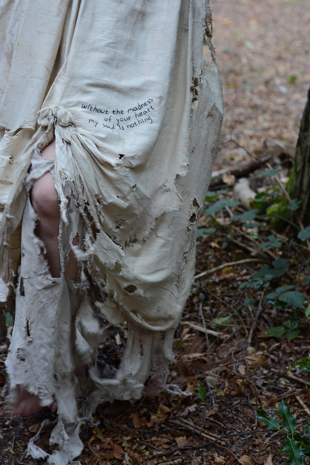 Detail of frayed hem with embroidered poetry